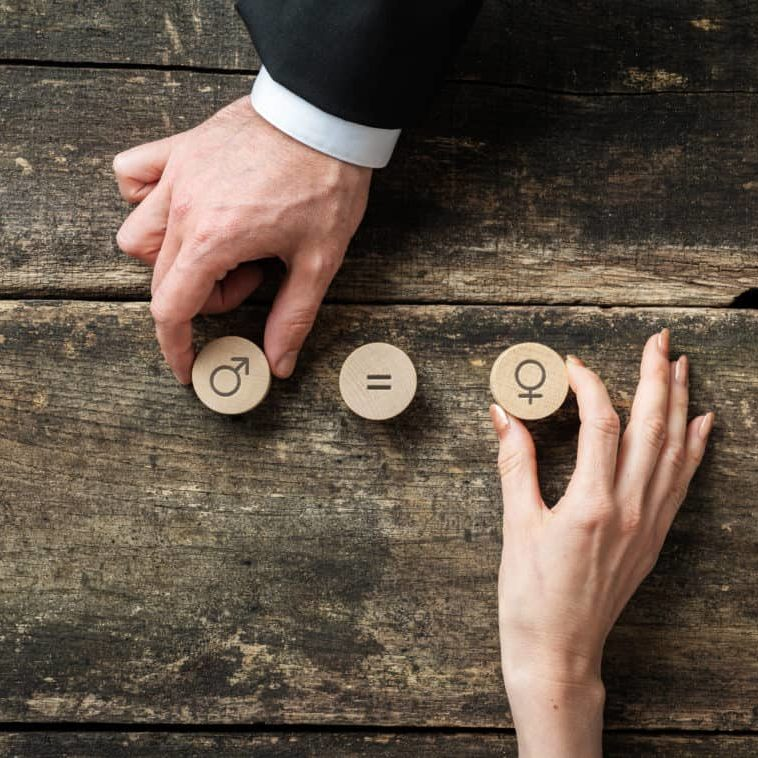 Gender equality conceptual image - male and female hand placing wooden cut circles with gender symbols over rustic wooden desk.